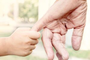 Child holding grand parents hand