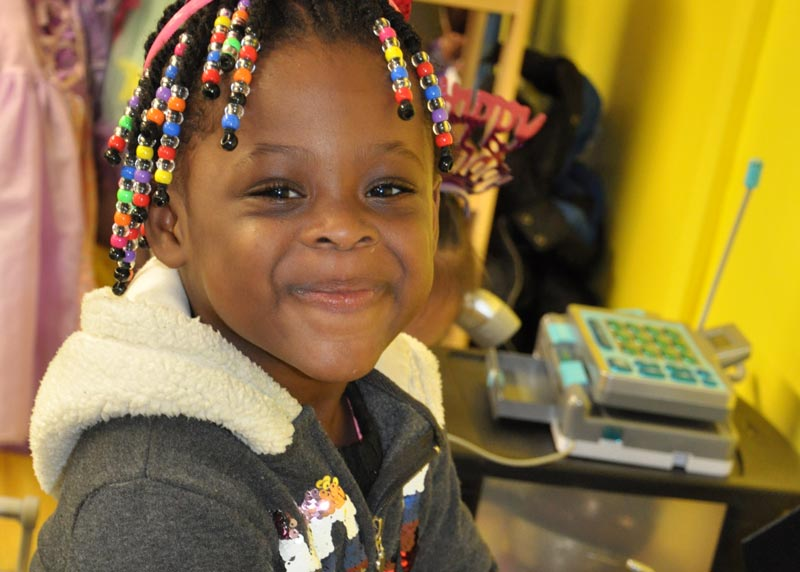 girl with beaded braids playing store in a classroom