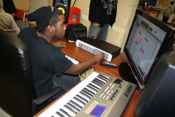 High School Sudent sitting at a computer and keyboard learning music production