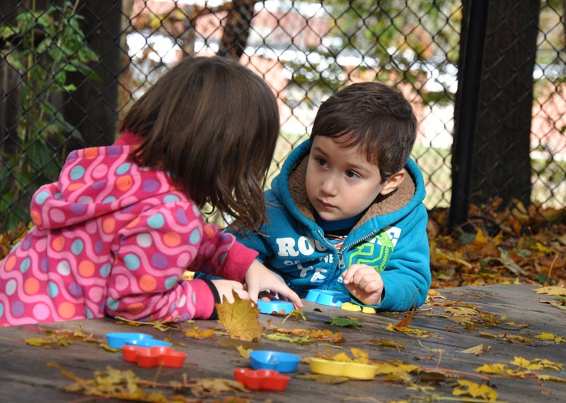 boy and girl in close conversation at outside table in the fall