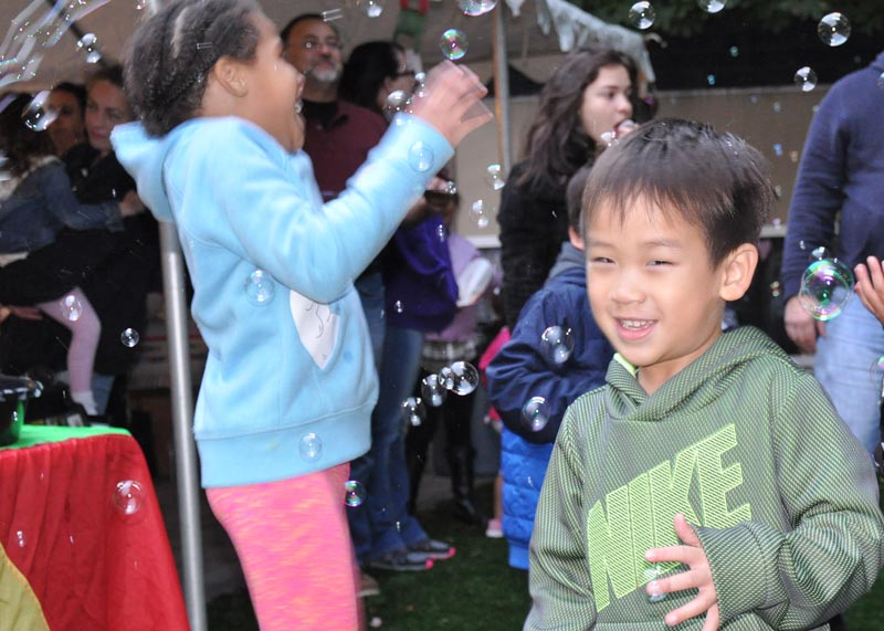black girl dancing in bubbles, Asian boy in hoodie in the foreground smiling