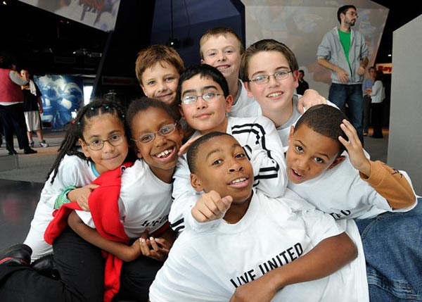diverse group of afterschool students smiling and posing for photo