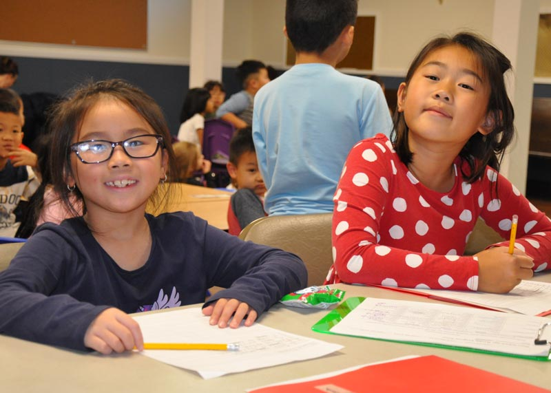 2 elementary schools students working on homework and smiling