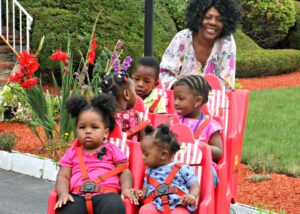 Caregiver pushing 5 kids in a jump stroller
