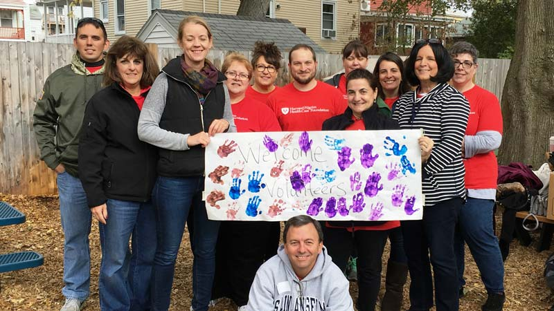 """Group of employees from Harvard Pilgrim on site at Stars Preschool holding banner that says """"Welcome Volunteers"""""""