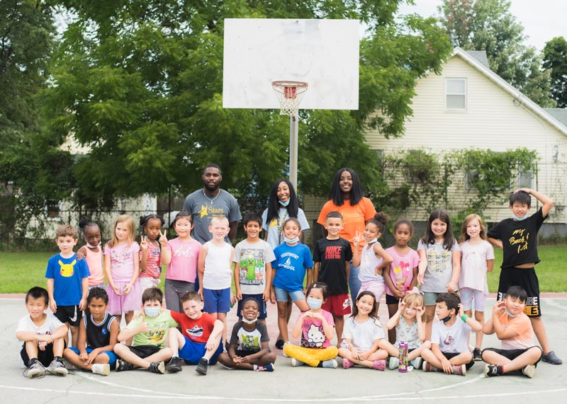 Diverse group of elementary school students grouped with their teachers on a basketball court outside at Stars Atlantic Afterschool program
