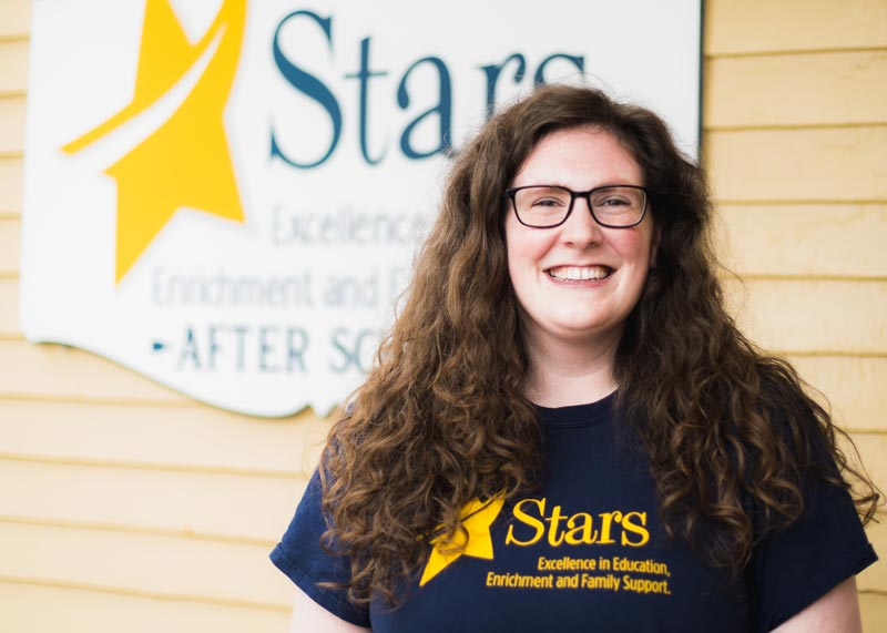 Stars Weymouth Afterschool program director in front of Stars sign