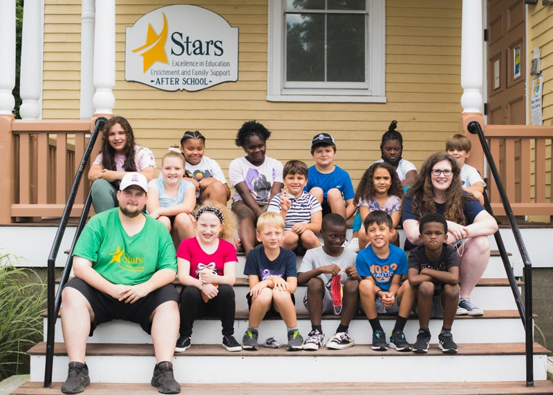 group of afterschool students from elementray to middleschool with teachers, sitting on steps outside Stars afterschool location