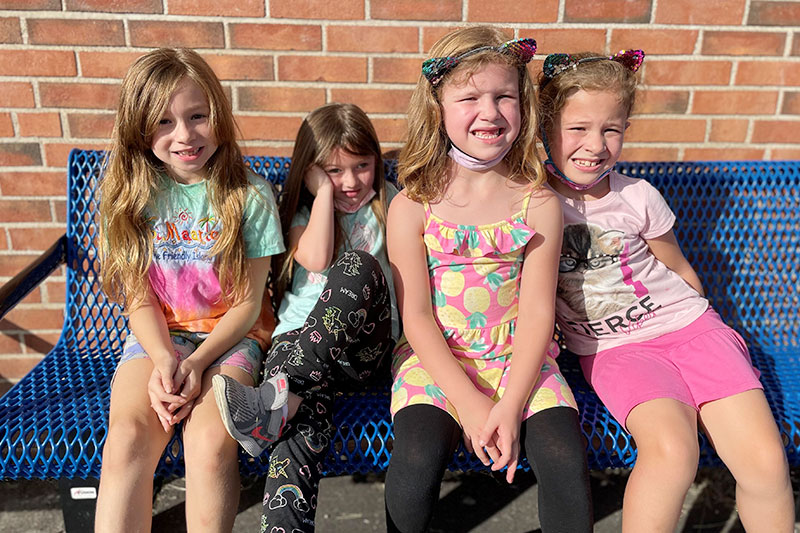 4 elementary school girls sitting on a bench laughing
