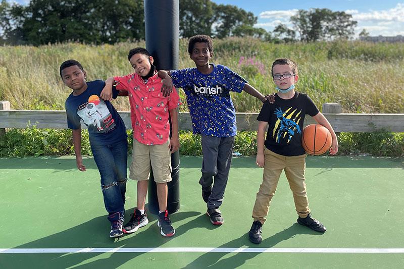 4 boys posing for photo on basketball court